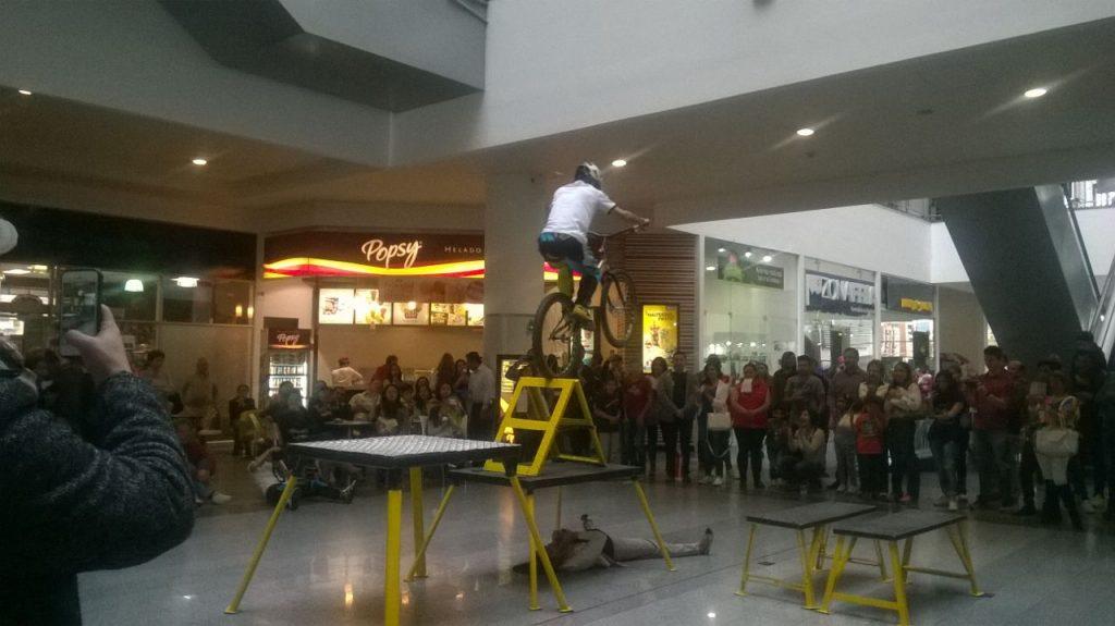Pacho Villegas en su show extremo subiendo a lo mas alto de un triangulo y descendiendo entre las piernas de un arriesgado asistente del publico